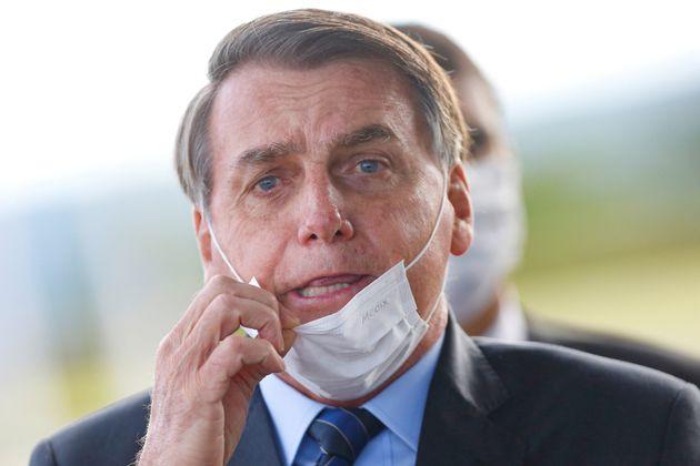 Brazil's President Jair Bolsonaro adjusts his mask as he leaves Alvorada Palace, amid the coronavirus...