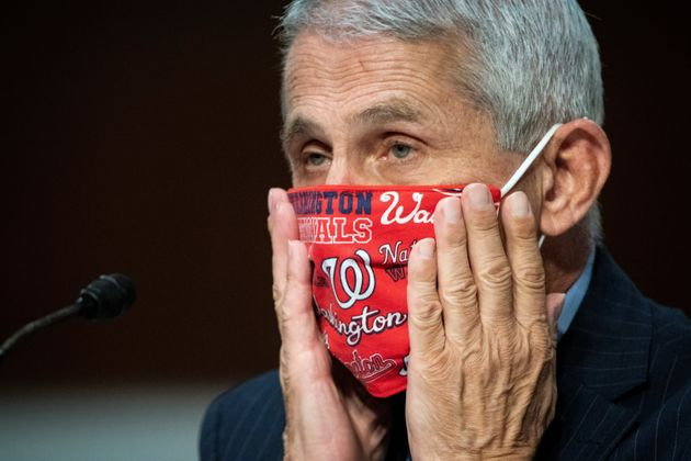 Anthony Fauci, director of the National Institute of Allergy and Infectious Diseases, adjusts his face...