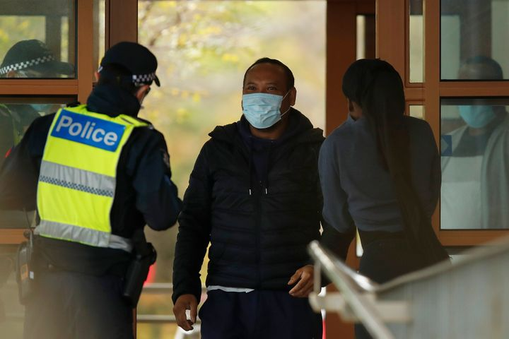 MELBOURNE, AUSTRALIA - JULY 07: People speak with police at the entrance to one of the public housing towers in Kensington on July 07, 2020 in Melbourne, Australia.