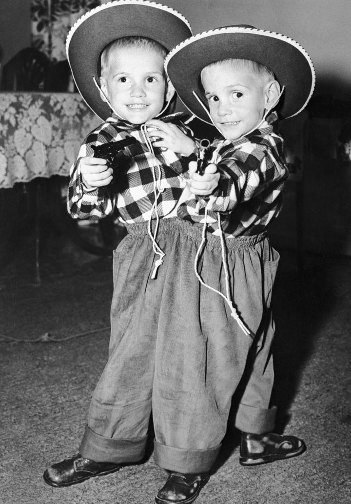 Siamese twins Ronnie and Donnie Galyon pose in their cowboy suits on their third birthday.