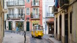 LISBON, PORTUGAL: Piaggio Ape tuk tuk type three-wheeler passenger vehicle and tram tracks, narrow steep shopping street in Alfama District, Lisbon, Portugal.  (Photo by Tim Graham/Getty Images)