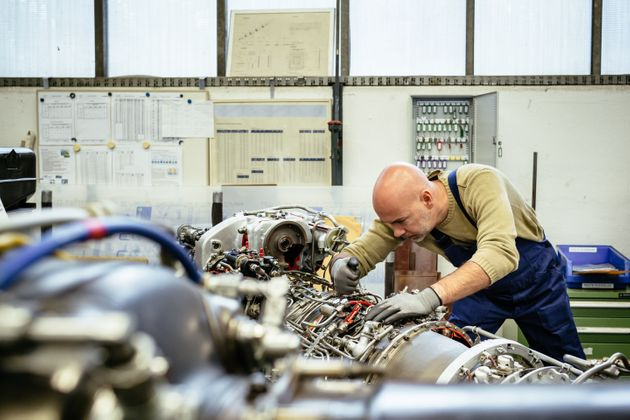 A mature male mechanic is working on open engine inside an aircraft hangar. Wires an cables of the machine...