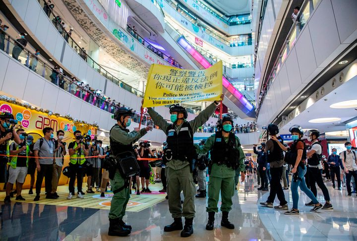 Riot police hold up a warning flag during a demonstration in a mall in Hong Kong on Monday, in response to a new national sec