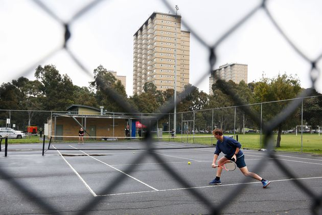 People play tennis near a block of public housing towers that residents have been banned from leaving,...