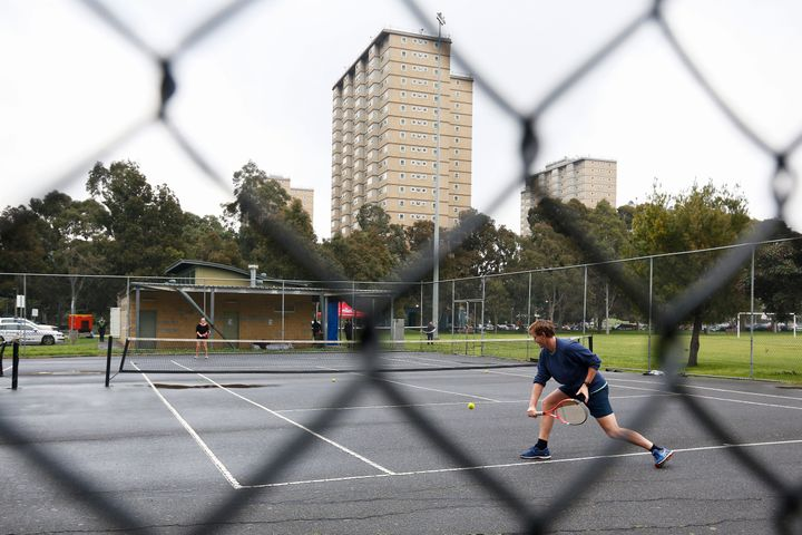 People play tennis near a block of public housing towers that residents have been banned from leaving, on Tuesday.