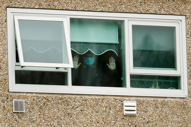 A man looking out a window of the locked-down housing complex on Monday in