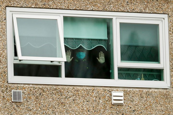 A man looking out a window of the locked-down housing complex on Monday in Melbourne.