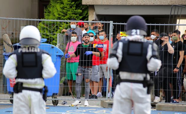 Police officers inGöttingen, Germany, face a group of residents quarantined inside a residential...