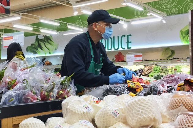 A grocery store worker wears a mask and gloves to protect himself from the novel coronavirus as he stocks...