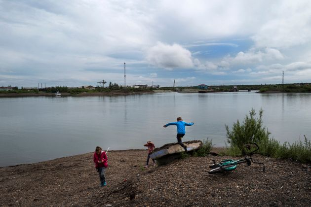 ZYRYANKA RUSSIA - JULY 5 Children play on the banks of the Kolyma River in the Siberian town of Zyryanka,...