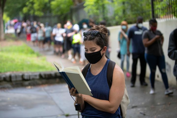 Kelsey Luker reads as she waits in line to vote on June 9 in Atlanta. Luker said she had been in line for almost two hours. V
