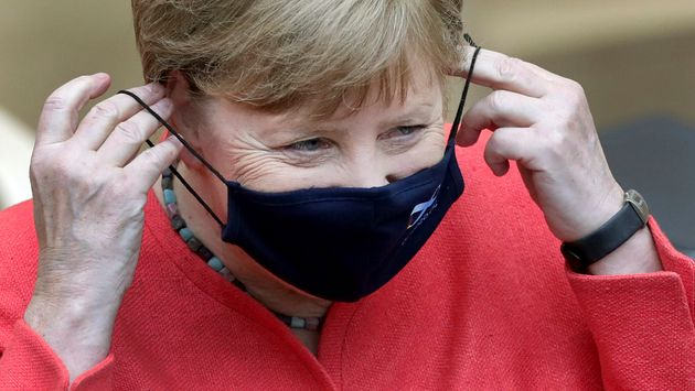 German Chancellor Angela Merkel adjusts her face mask as she arrives for a meeting of the upper house...