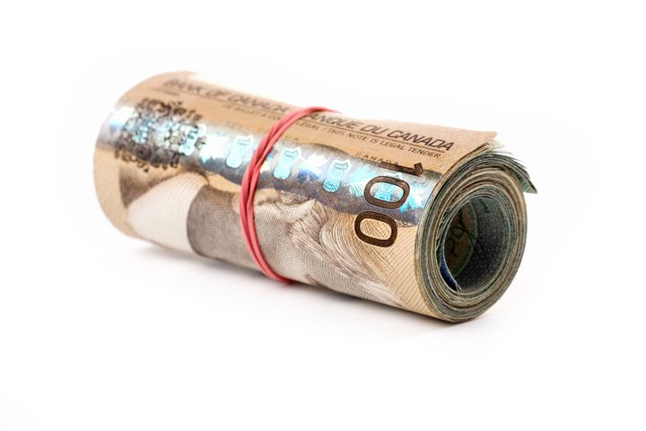 File photo of Canadian money wound up in a roll. The Parliamentary Budget Office estimates a six-month basic income program would cost at least $47.5 billion.