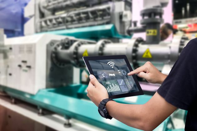 Hands holding tablet on blurred automation machine as