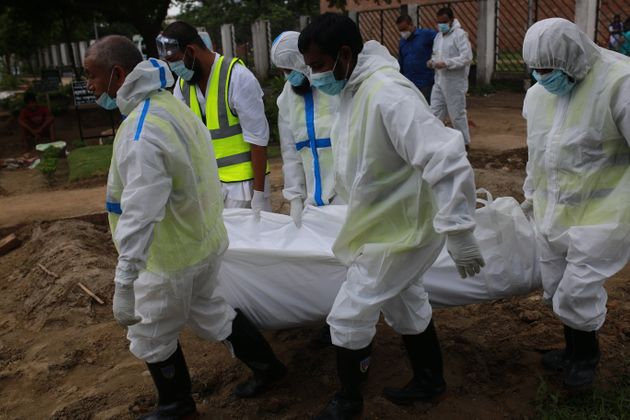 Volunteers wearing protective stuffs carry the body of a man who died from the COVID-19 coronavirus infections...