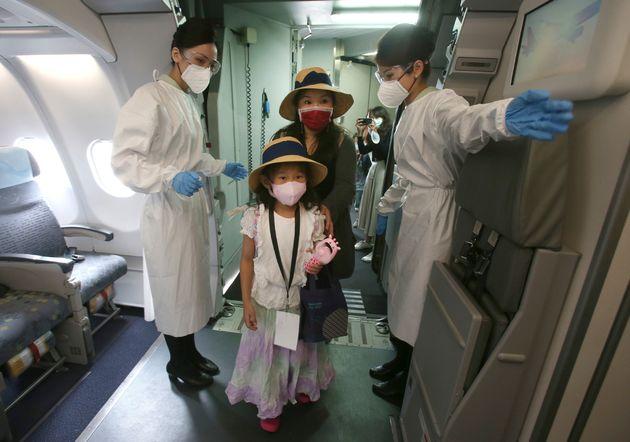 보호복을 착용한 승무원들이 '비행 체험' 행사에 참가한 승객들을 맞이하고 있다.타이베이, 대만. 2020년