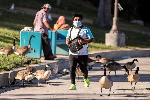 Un hombre corre con mascarilla en el parque MacArthur en Los Ángeles (EEUU), el 21 de mayo