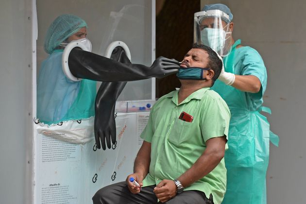 Health officials collect a swab sample from a man to test for COVID-19, at a testing centre in