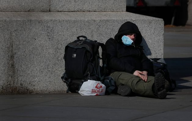A man sleeps on the pavement in Westminster in London, British people have been told to stay home to...