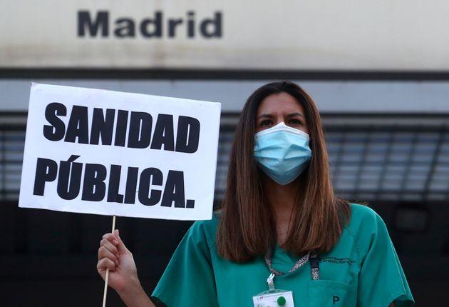 Una médica del hospital universitario Gregorio Marañón sujeta una pancarta que dice...