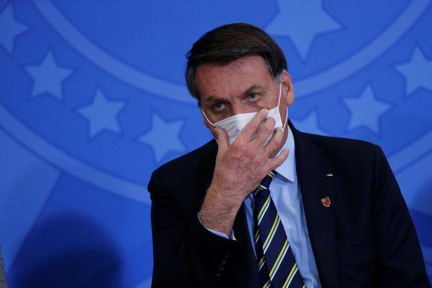 Presidente Bolsonaro utiliza máscara de forma inadequada em evento no Planalto.O uso é...