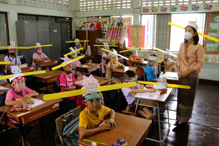 A teacher and students wearing hats designed to help them practice social distancing at a school in Thailand.