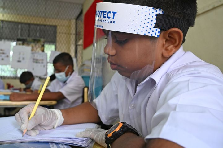 A student wearing a face shield attends school in Sri Lanka after their school was reopened this week.