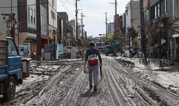 泥に覆われた道路を歩く男性=8日午前、熊本県人吉市
