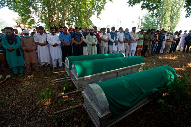 Relatives and BJP workers offer funeral prayers in front of the coffins of BJP leader Waseem Bari, his...