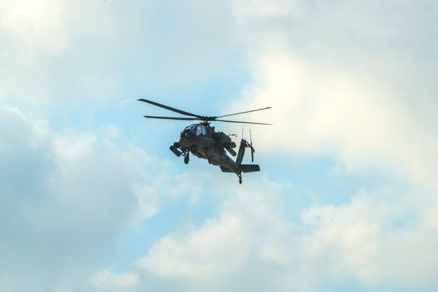 An Apache Helicopter Flying Over Blue