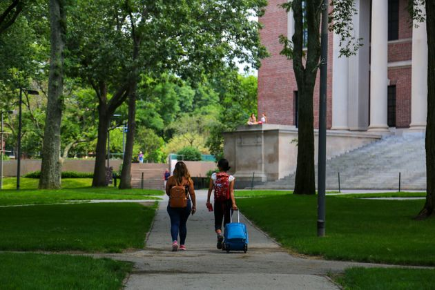Two students leave their campus with baggage at Harvard University in Cambridge, Mass. on July 8,