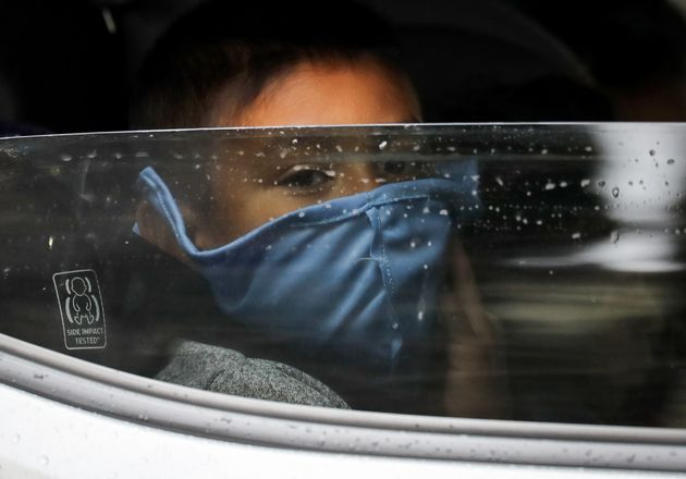A boy wears a face mask as food is delivered to his family's truck at a food bank distribution center...