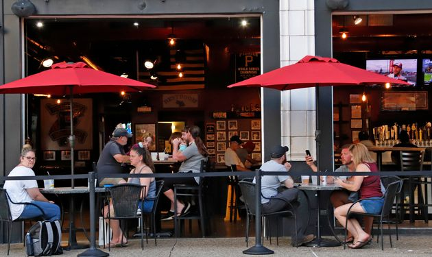 People eat inside and outside at a Pittsburgh restaurant on June 28. The WHO noted multiple reported...