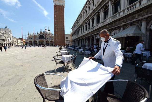 A waiter sets a table on June 12 at the terrace of the 18th Century Cafe Florian on St. Mark's Square...