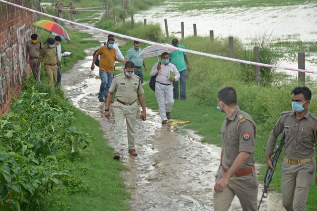 Policemen arrive at the scene to investigate after gangster Vikas Dubey was shot dead by police in Uttar...