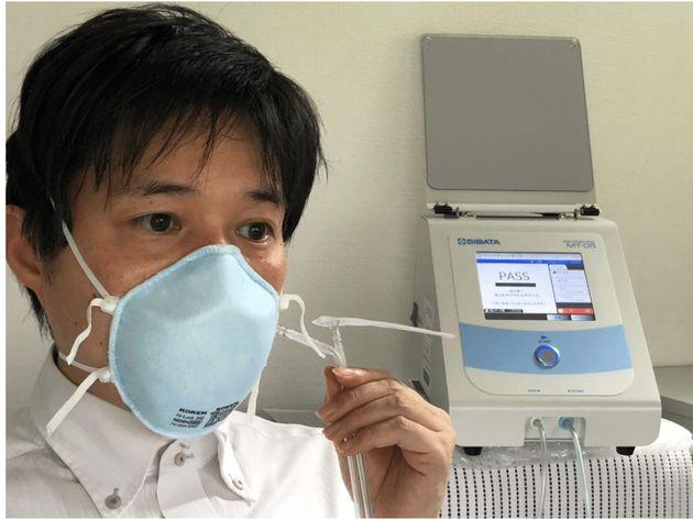 専用装置でマスク内への粒子の侵入率を測定する大西一成准教授