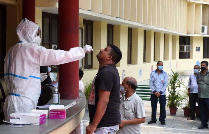 A health worker collects a swab sample for the Rapid Antigen Test for Covid-19 at Happy School at Daryaganj on July 3, 2020 in New Delhi.