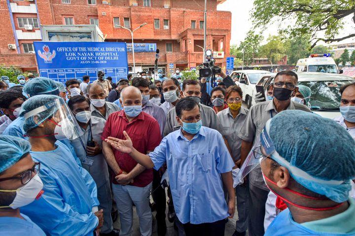 Delhi Chief Minister Arvind Kejriwal and Deputy CM Manish Sisodia talk to the medical workers at Lok Nayak Jai Prakash Narayan Hospital on June 25, 2020 in New Delhi.