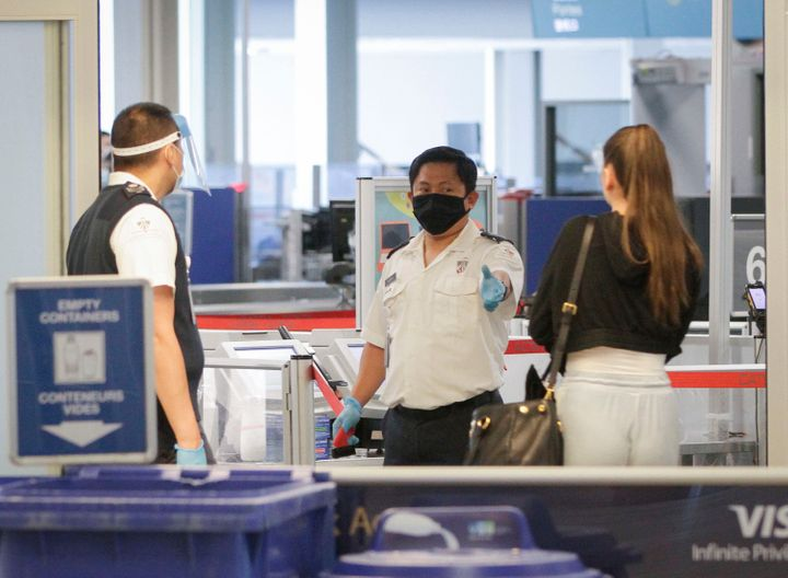 Border officers are seen wearing masks and a face shield at a security screening of Vancouver International Airport in Vancouver, British Columbia, Canada, on June 18, 2020.