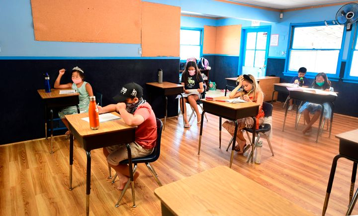 Children in an elementary school class wear masks and sit as desks spaced apart during summer school at Happy Day School in M