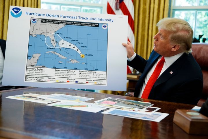 President Donald Trump holds a chart on Sept. 4, 2019, as he talks with reporters after receiving a briefing on Hurricane Dor