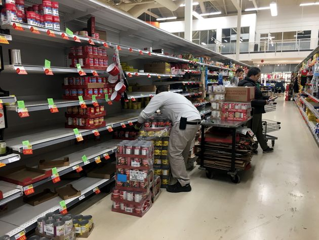 A worker restocks grocery store shelves with canned goods early in the morning in Toronto on March 13,