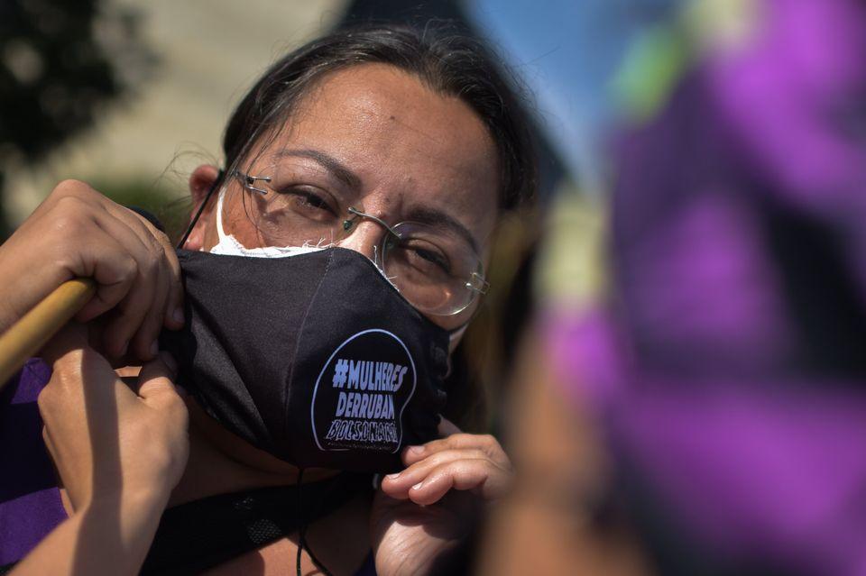 Mulher utiliza máscara de proteção em protesto na Esplanada dos Ministérios,...