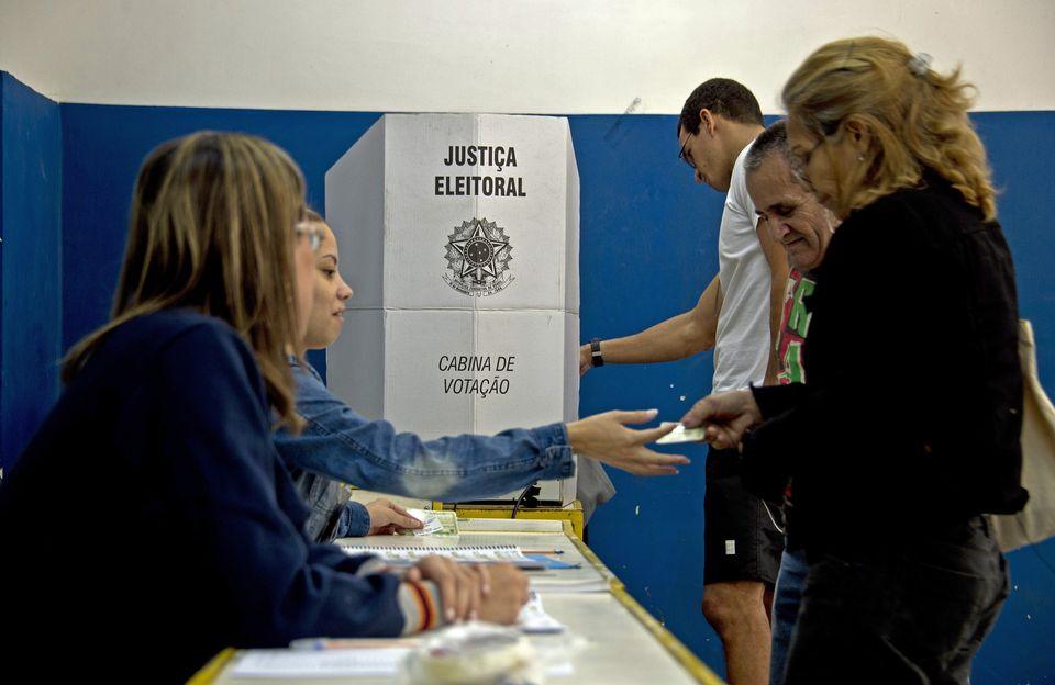 Eleitores votam no Colégio Municipal Ayrton Senna, ao lado da favela da Rocinha, no Rio de Janeiro,...