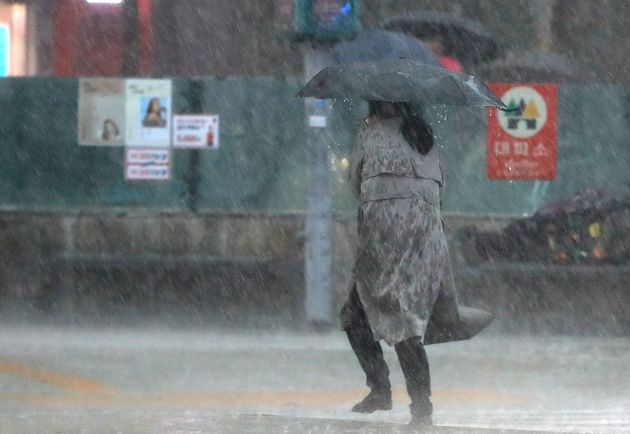 지난 5월 서울 광화문네거리에서 시민들이 갑자기 내린 폭우에 발걸음을 옮기고