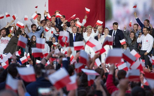 Polish President and presidential candidate Andrzej Duda greets his supporters following the announcement...