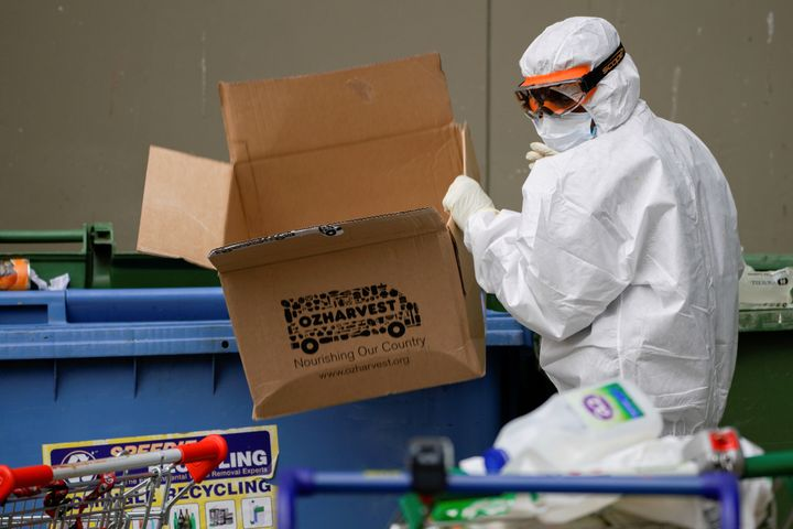 A worker dressed in personal protective equipment disposes of rubbish outside a public housing tower, reopened the previous night after being locked down in response to an outbreak of the coronavirus disease (COVID-19), in Melbourne, Australia, July 10, 2020. REUTERS/Sandra Sanders