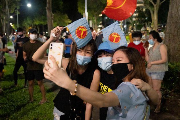 싱가포르 야당 노동자당의 지지자들이 총선 출구조사 결과 발표에 환호하며 사진을 찍고 있다. 2020년
