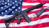 Custom built AR-15 carbine, bullets and a magazine on American flag surface, background. Studio shot