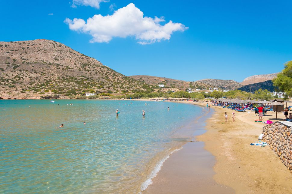 Syros, Greece/ July, 2018: People swimming in the turquoise waters of Galissas beach at Syros cycladic island in Greece